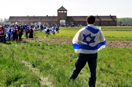A man draped in the Israeli flag contemplates the horrors of the Auschwitz extermination camp in Poland.  Approximately one in six Jews who were killed in the Holocaust died here