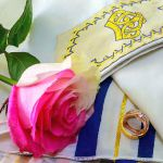 Wedding rings and roses on prayer shawl