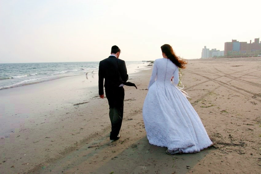 A Jewish bride and groom take a walk beside the ocean together for the first time as man and wife.