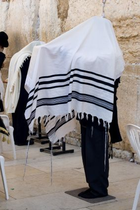 Some tallits (prayer shawls) are large enough to be draped over the head while praying.  In the photo above, the tzitzit are visible on the four corners of the garment hanging down.