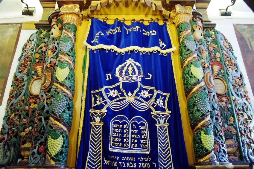 The Parokhet (embroidered curtain) can be either inside or outside the Aron Kodesh (Holy Ark).  Some of these cabinets are built around a theft and fireproof safe.