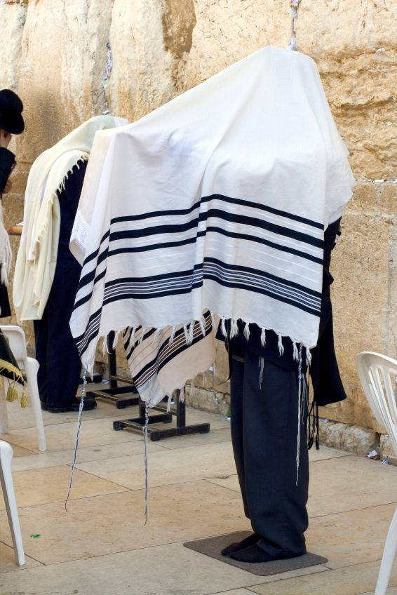 A descendant of Aaron recites the Priestly Blessing over the congregation at the Western (Wailing) Wall.  This is done with the shoes removed, hands washed, head covered with the tallit (prayer shawl), and hands outstretched toward the congregation.