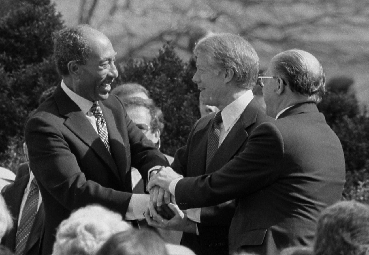 President Jimmy Carter shakes hands with Egyptian President Anwar Sadat and Israeli Prime Minister Menachem Begin at the signing of the Egyptian-Israeli Peace Treaty on the grounds of the White House.
