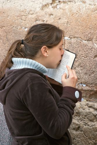 A young Jewish woman kisses the siddur (Jewish prayer book) while praying at the Western (Wailing) Wall in Jerusalem.