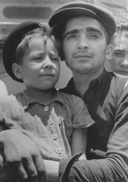Eight-year-old Yisrael Meir (Lulek) Lau is held by a fellow Buchenwald survivor, Elazar Schiff, as they arrive in Palestine Israel aboard the RMS