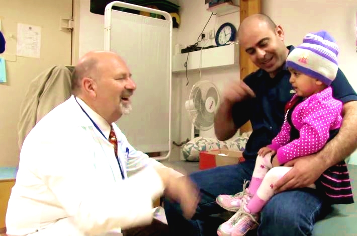 Wallah, a Gaza toddler who underwent emergency surgery at Israel's Rambam Hospital for a massive tumor that was pressing on her brain, sits on her father's lap as she talks to her Israeli doctor.  (YouTube capture)