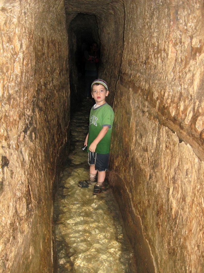 A Jewish lad explores Hezekiah's tunnel with a flashlight in hand.