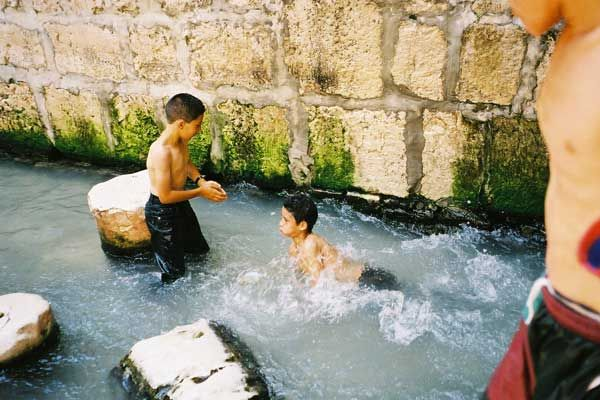 Israeli children, who have exited Hezekiah's Tunnel at the Pool of Siloam, play in the water that originates at the Gihon Spring.