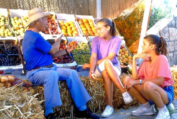 Israeli girls befriend a fruit vendor (Photo: Go Israel)