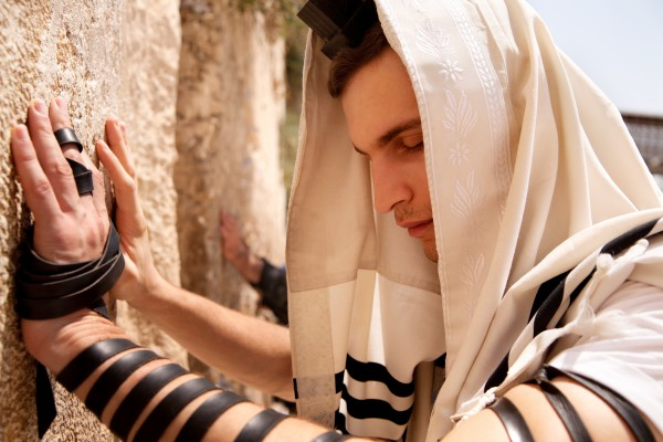 A Jewish man prays at the Western (Wailing) Wall wearing tefillin (phylacteries). (Photo credit: Go Israel, Noam Chen)