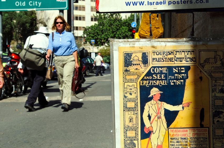 Pedestrians walk past an antique tourism poster for sale outside a shop on a Jerusalem street.  The poster is written in Hebrew and English and uses both the terms Palestine and Eretz Israel.