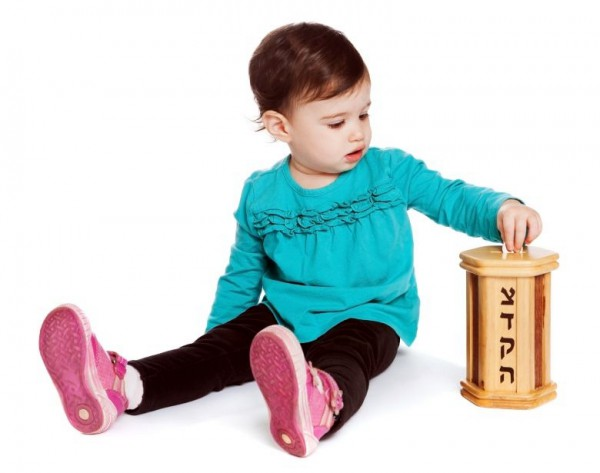 Toddler puts charity in the tzedakah (pushke) box