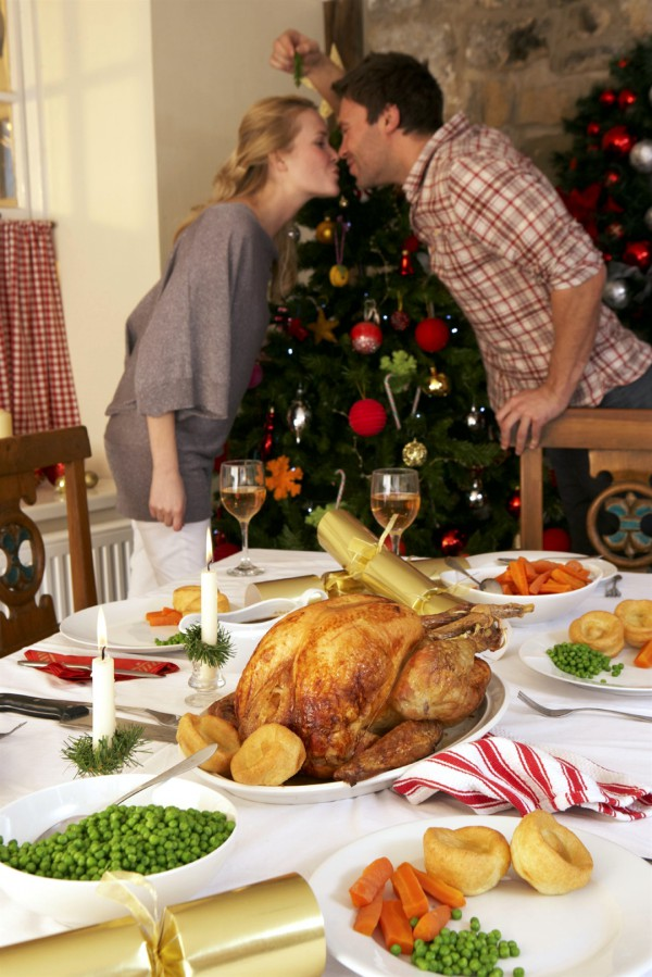 With Christmas dinner on the table, a young couple kisses under the mistletoe.