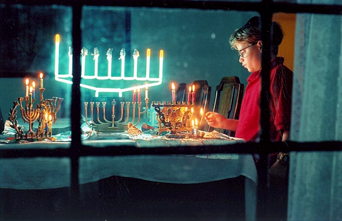 A Jewish boy lights multiple Hanukkah menorahs on the second night of Hanukkah, as a neon menorah glows in the background.