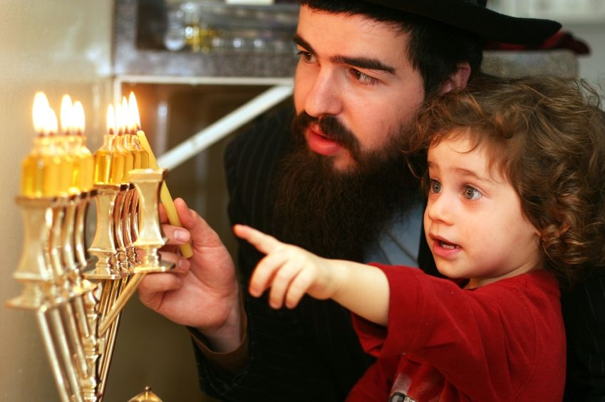 A Jewish child watches as his father kindles the eight lights on theHanukkah menorah, also called the Hanukkiah.