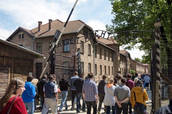 """Visitors pass through a gate at Auschwitz that promises """"Arbeit Macht Frei"""" (work makes [you] free). A great many Holocaust victims were literally worked to death by the Nazis."""