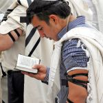 Jewish men wearing tallitot (prayer shawls) pray with tefillin (phylacteries) and siddurim (Jewish prayer books).