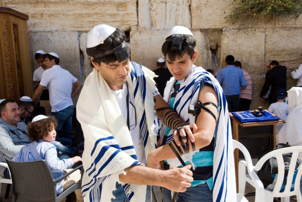 A Jewish man at the Western (Wailing) Wall helps a young man, perhaps his son, to wrap tefillin (phylacteries).