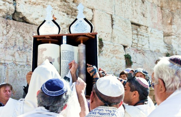 Jewish men pay reverence to the Torah at the Western (Wailing) Wall.