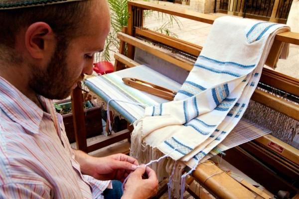 A Jewish artisan who weaves tallitot ties the tzitzit to the four corners of the garment. (Israel photo gallery by Noam Chen)