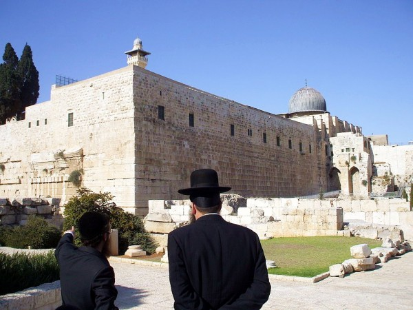 An Orthodox Jewish man points to the remains of Robinson's Arch, a monumental staircase built by Herod that was supported by an unusually wide stone arch. It stood at the southwestern corner of the Temple Mount.