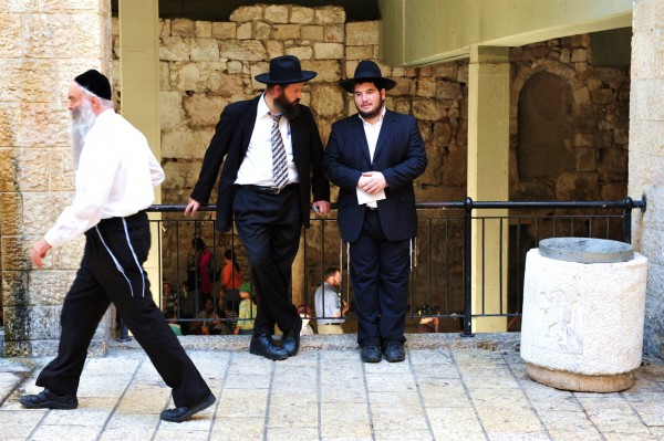 The tzitzit of the tallit katans of two Jewish men are worn outside, while the third man has tucked in his tzitzit.