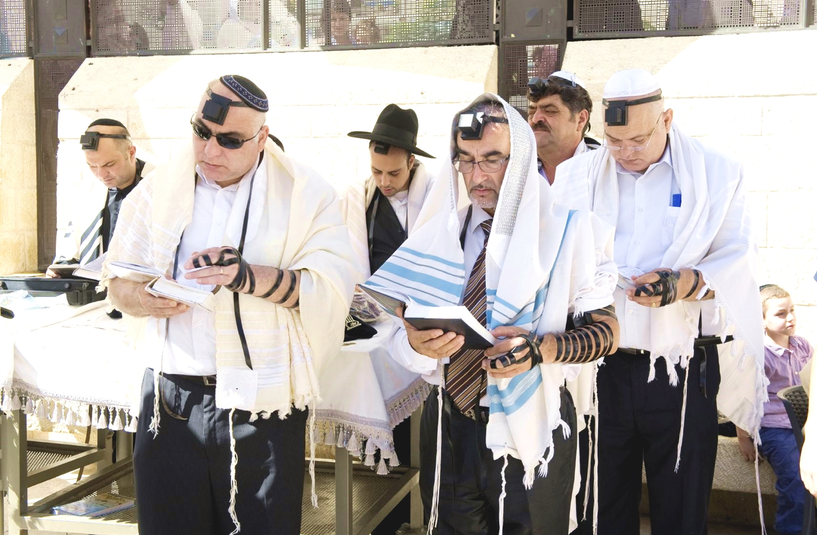 Jewish men wearing tallitot pray at the Western (Wailing) Wall in Jerusalem.