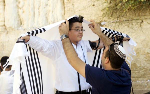 A Jewish father helps his son adjust his tallit gadol during the boy's bar mitzvah at the Western (Wailing) Wall.