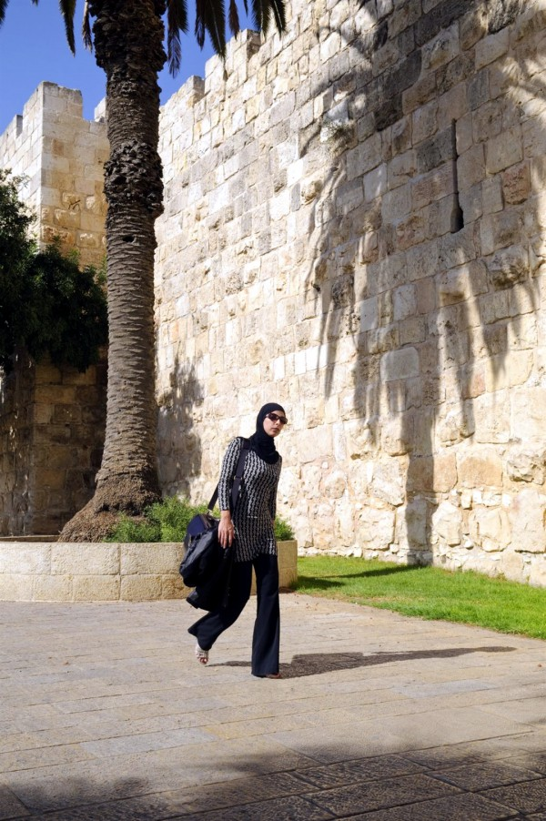 A Palestinian woman walks past the Old City walls of Jerusalem, between the New and Jaffa Gates.