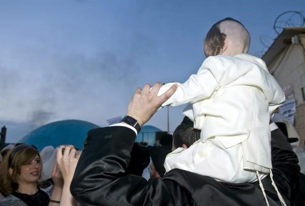A three-year-old boy wears a tallit katan under his shirt.