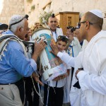 A 13-year-old Jewish boy carries the Torah scroll at the Western (Wailing) Wall as the adults venerate the Torah by kissing the Torah tik (ornate box protecting the Torah scroll).