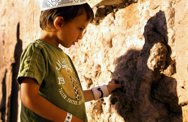 An Israeli child inserts a written prayer into the crevices of the Western (Wailing) Wall, a tradition that arose after the destruction of the Holy Temple, which was situated behind this wall. (Go Israel photo by Noam Chen)