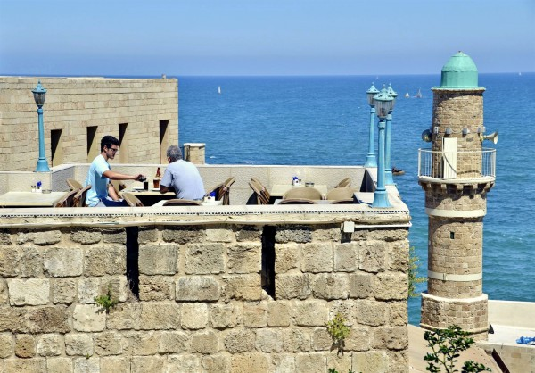 People have a bite to eat on a restaurant patio in Jaffa, Israel.