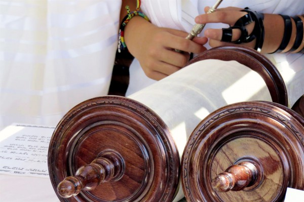 A Jewish youth prepares to read from the Torah scroll.