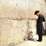 A child sits at her father's feet as he prays at the Western (Wailing) Wall in Jerusalem. (Israel Tourism photo by VuTheara Kham)