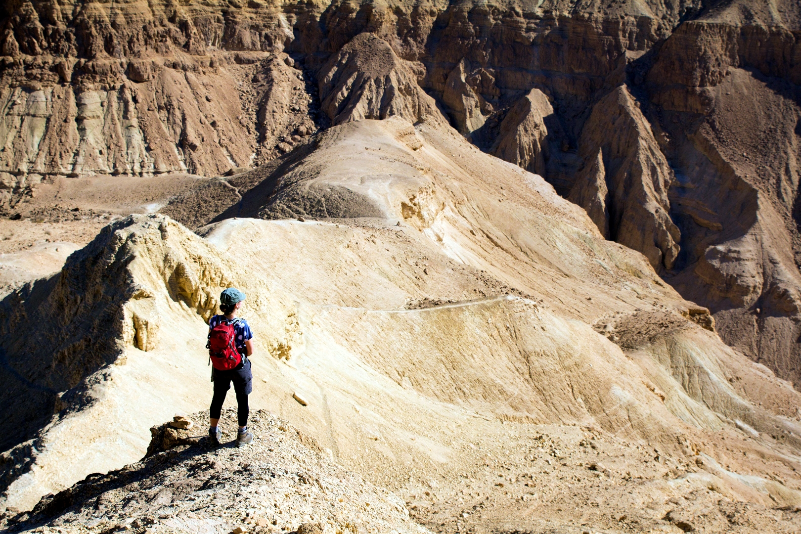 A woman stands on a mountain peak in Israel's desert.