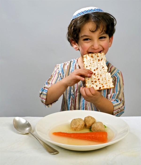 A Jewish boy eats a piece of matzah. Before him is a bowl of matzah ball soup.