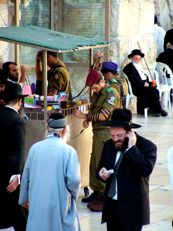 Israeli soldiers wrap tefillin (phylacteries) at the Western (Wailing) Wall for morning prayer.