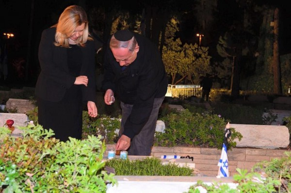 Prime Minister Benjamin Netanyahu and his wife Sara pay tribute to Israel's fallen soldiers at the Mount Herzl cemetery in Jerusalem, lighting a candle for Yonatan Netanyahu.