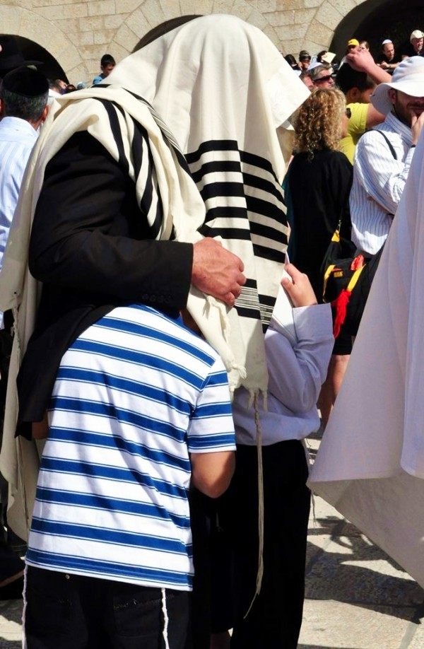 A father pulls his sons under his tallit (prayer shawl) during the Priestly Blessing at the Western Wall in Jerusalem. (Photo by Lilach Daniel)