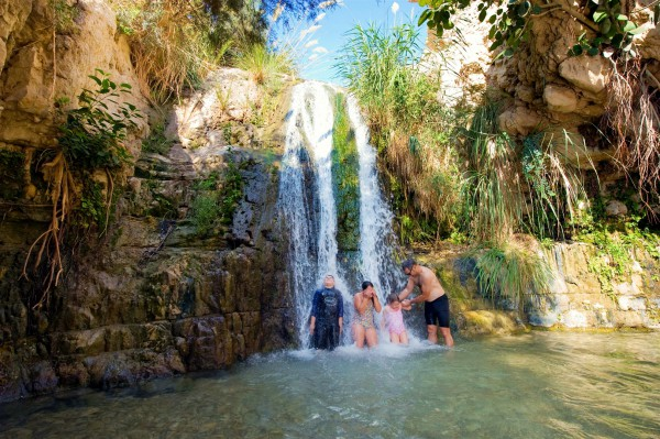 A father and his children refresh themselves at the Ein Gedi oasis, which is near Masada and the Dead Sea.