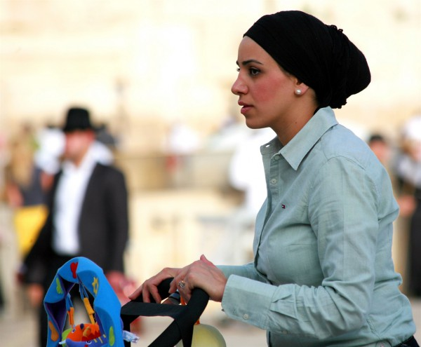 An Orthodox Jewish mother pushes a stroller in Jerusalem. (Photo by opalpeterliu)