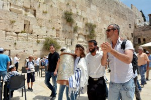 A 13-year-old Jewish teen carries the Torah scroll at the Western (Wailing) Wall in Jerusalem.