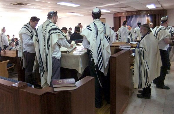 Jewish men read Scripture during morning prayer in an Israeli synagogue.