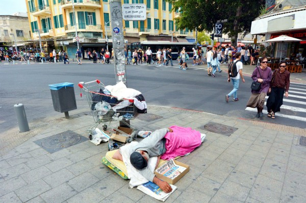 A homeless man sleeps on a street corner in Tel Aviv.