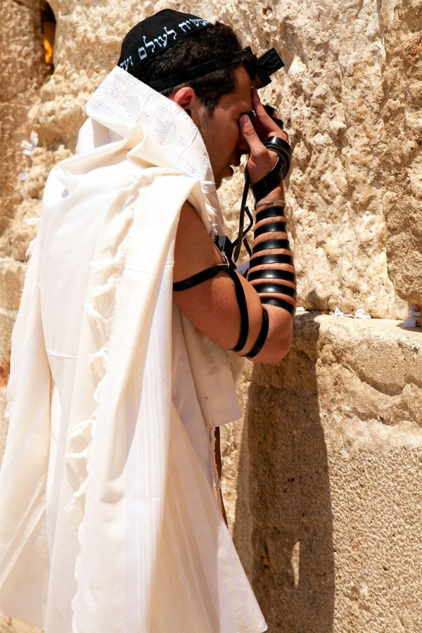 A Jewish man prays at the Wailing (Wailing) Wall in the Old City of Jerusalem wearing a tallit (prayer shawl), a kippah (head covering), and tefillin (phylacteries). (Israeli Ministry of Tourism photo by Noam Chen)