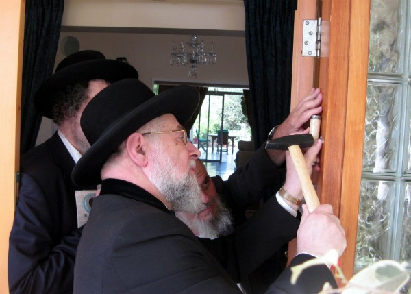 "Tel Aviv-Jaffa Chief Rabbi Lau affixes a mezuzah (doorpost) to the front door of the British Ambassador to Israel's Ramat Gan residence in fulfillment of the Biblical injunction to inscribe the words of the Shema ""on the doorposts of your house (Deuteronomy 6:9)."" The parchment, which is protected in a decorative case, is inscribed with Deuteronomy 6:4–9 and 11:13–21."