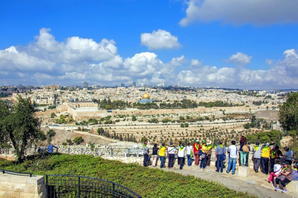 Tourists on the Mount of Olives look toward the Temple Mount where the First and Second Jewish Temples once stood in Jerusalem.