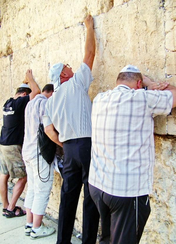 Jewish men pray at the Western (Wailing) Wall in Jerusalem, where it is traditional to stuff prayers on slips of papers in the crevices of the wall.