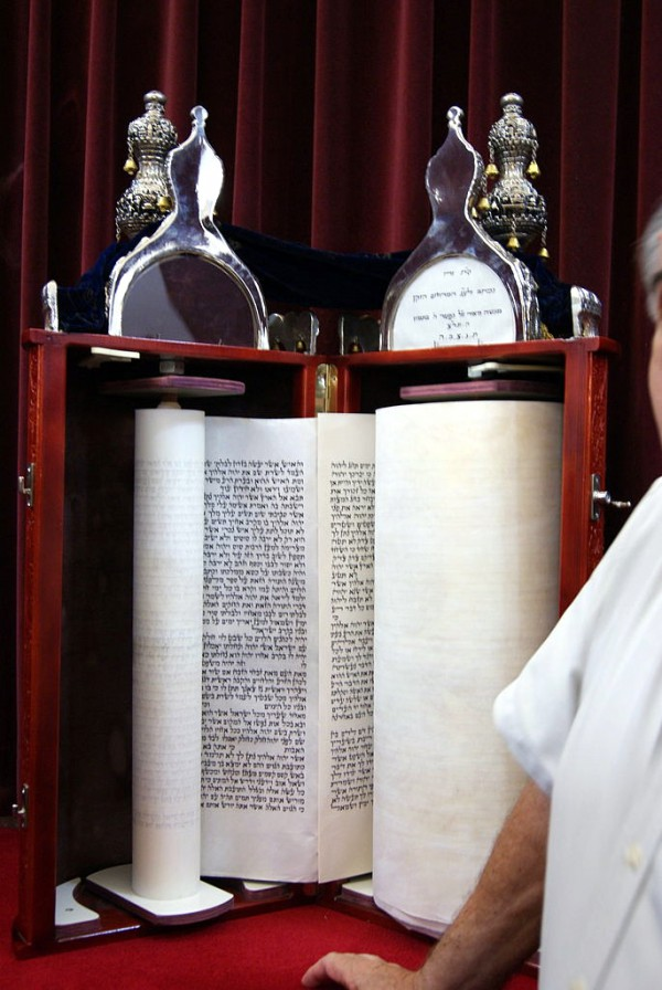 Reading from a Torah scroll encased in a protective Torah tik.